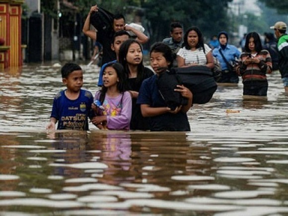 Residents walking along a flooded road as they evacuate Dayeuhkolot village in Bandung. (Photo: AFP)