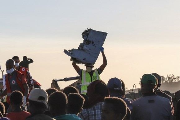 A man carries a piece of debris on his head at the crash site of a Nairobi-bound Ethiopian Airlines flight near Bishoftu, a town some 60 kilometres southeast of Addis Ababa, Ethiopia, on March 10 (Source: AFP)