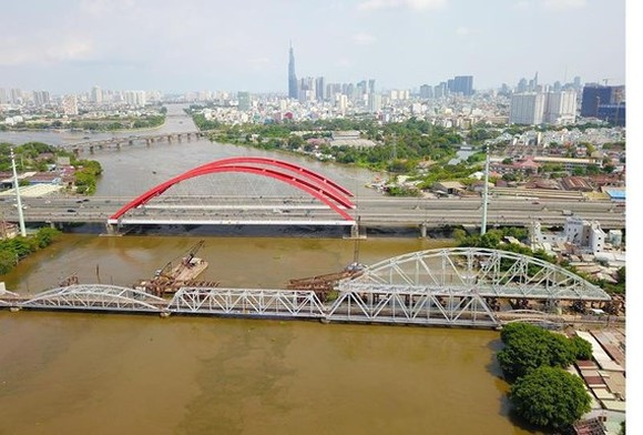 New Binh Loi Bridge is under construction in HCMC with the height from the water surface to the bridge much higher than the old adjacent one (Photo: SGGP)