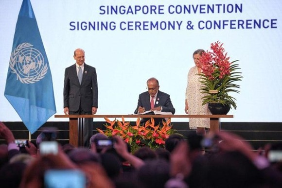 Home Affairs and Law Minister K. Shanmugam signing the Singapore Convention on Aug 7, 2019. (Source: www.straitstimes.com)