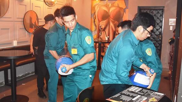 Đội tuần tra liên ngành quận 1, TPHCM và phường Phạm Ngũ Lão  lập biên bản tạm giữ các bình khí N2O tại một quán bar trên đường                Nguyễn Quang Đẩu vào khuya 29-9-2018.        Ảnh: QUANG HUY