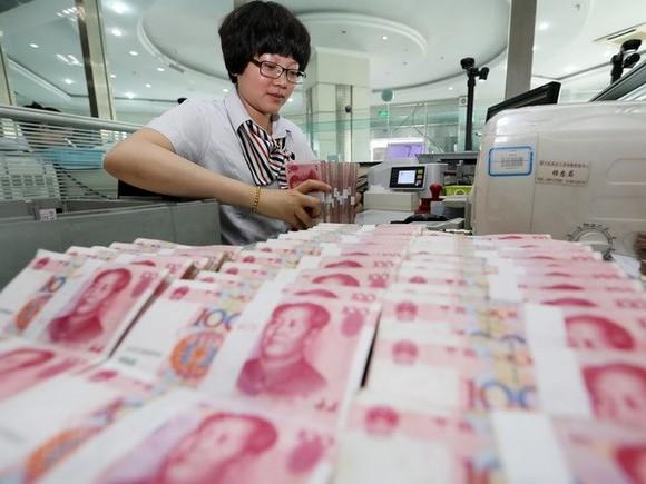 Kiểm tiền NDT tại ngân hàng ở Lianyungang, tỉnh Giang Tô, miền Đông Trung Quốc ngày 11-8. Nguồn: TTXVN