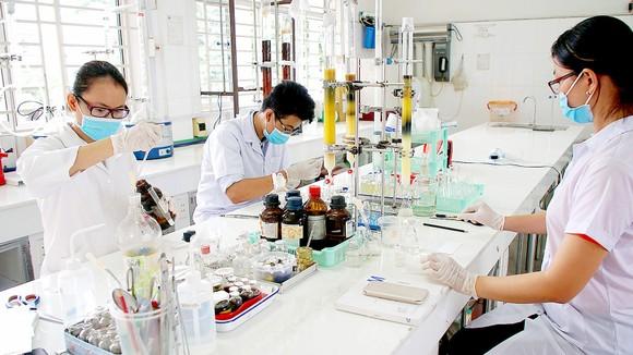 Sinh viên Trường Đại học Sài Gòn nghiên cứu hóa học tạo vi sinh bảo vệ môi trường. Ảnh: HOÀNG HÙNG
