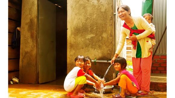 Bà H'Nhêr (dân tộc M'Rông) và con cháu bên dòng nước sạch  được kéo về tận nhà