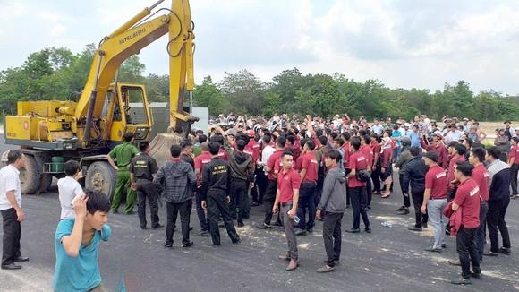 Nhân viên Công ty Alibaba cản trở lực lượng cưỡng chế sai phạm ở xã Tóc Tiên. Ảnh: NÔNG NGÂN