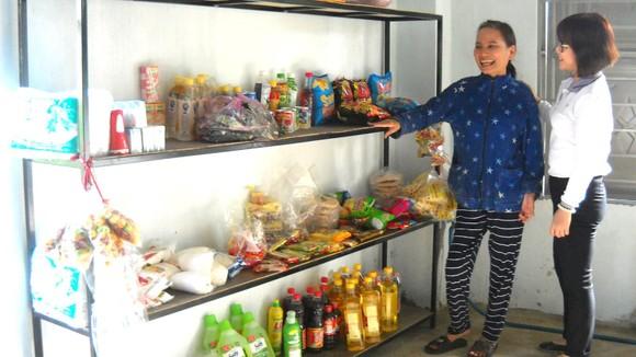 Chị Diệu trước kệ bán hàng do chị Nhung (bên phải) tặng