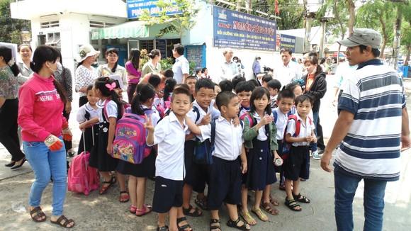 Học sinh Trường Tiểu học An Hội (quận Gò Vấp) được nhân viên một cơ sở bán trú hướng dẫn di chuyển về cơ sở nghỉ trưa