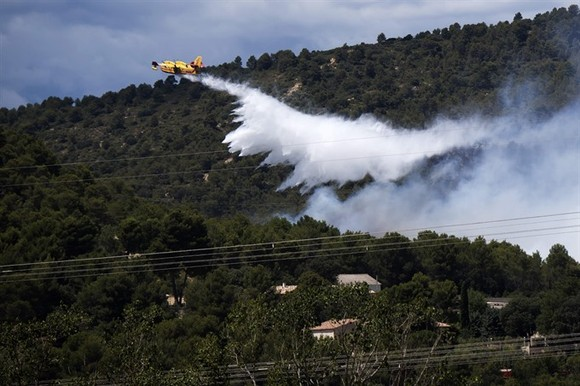A fire fighting Canadair aircraft drops water over a fire in Mirabeau, southeastern France, on Monday -AFP/VNA