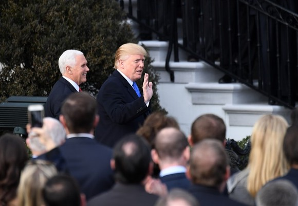 US President Donald Trump (R, rear) and Vice President Mike Pence (L, rear) arrive at an event celebrating the passage of the tax bill on the South Lawn of the White House in Washington DC, the US, on Wednesday.