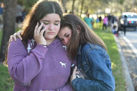 Students react following a shooting at Marjory Stoneman Douglas High School in Parkland, Florida, a city about 50 miles (80 kilometers) north of Miami on February 14, 2018. A gunman opened fire at the Florida high school, an incident that officials said c