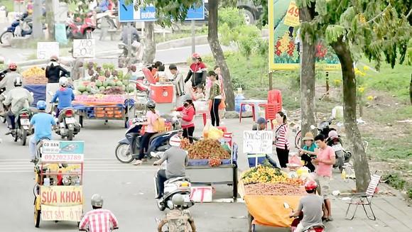 Xe hàng rong buôn bán lấn chiếm lòng đường quốc lộ 1A đoạn qua huyện Bình Chánh. Ảnh: THÀNH TRÍ