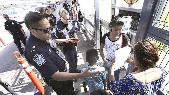 Nhân viên hải quan Mỹ kiểm tra giấy tờ người di cư tại khu vực biên giới. Ảnh: Washington Examiner