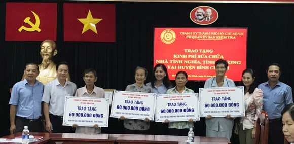 Lãnh đạo Ủy ban Kiểm tra Thành ủy TPHCM và các hộ dân tại buổi trao tặng kinh phí. Ảnh: KIỀU PHONG