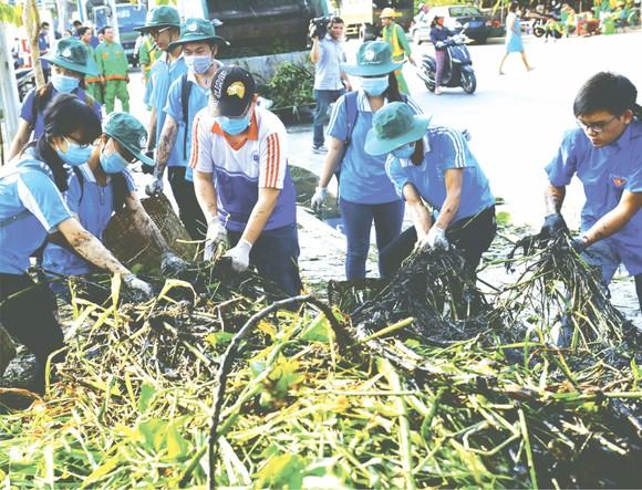 本市共青團員打掃街道保護環境潔淨。(圖片來源:光定)