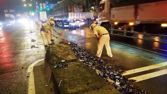 Cảnh sát giao thông hỗ trợ công nhân vệ sinh thu dọn vỏ chai đổ trên đường ảnh 1