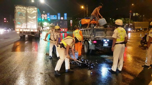 Cảnh sát giao thông hỗ trợ công nhân vệ sinh thu dọn vỏ chai đổ trên đường ảnh 3