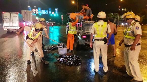 Cảnh sát giao thông hỗ trợ công nhân vệ sinh thu dọn vỏ chai đổ trên đường ảnh 2