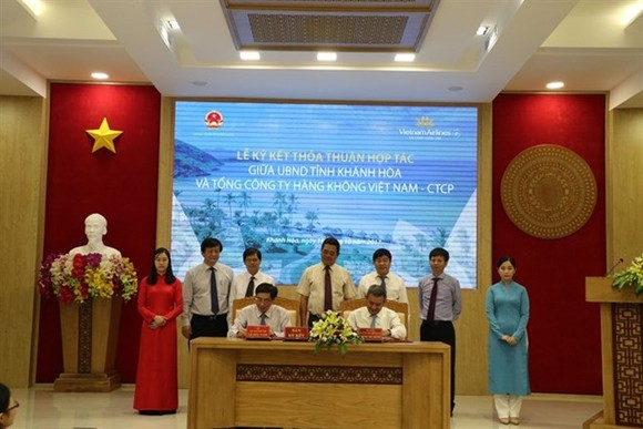 Chairman of Khanh Hoa province's People's Committee Le Duc Vinh (L) and General Director of Vietnam Airlines Duong Tri Thanh sign a deal on tourism development. (Photo: VNA)