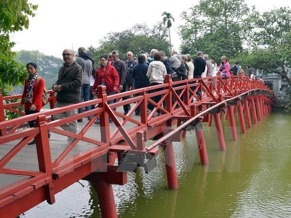 """Tourists stand on """"The Huc"""" Bridge, which leads to Ngoc Son Temple on Hoan Kiem Lake in Hanoi (Photo: VNA)"""