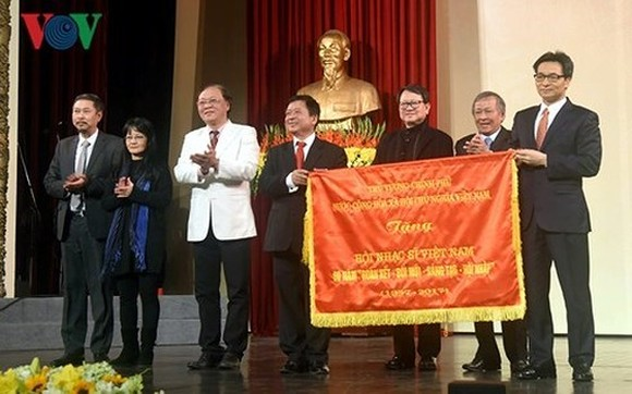 Deputy PM Vu Duc Dam offers certificate of merit to the Vietnam Musicians' Association. (Photo: VOV)