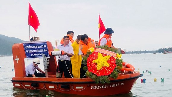 Truong Sa war veterans drop a wreath of flowers into the sea to commemorate Gac Ma fallen soldiers. (Photo: Sggp)