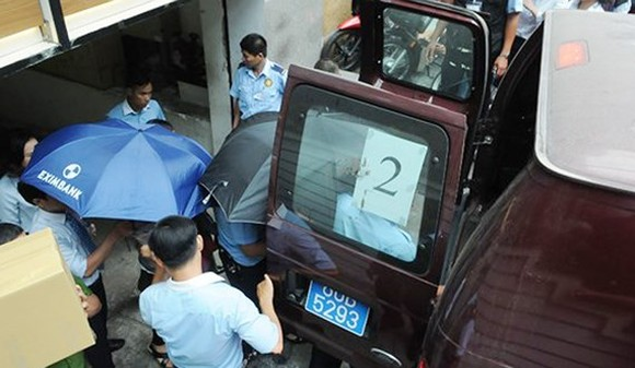 Officers from the Ministry of Public Security arrest two employees of Eximbank's Ho Chi Minh City branch. (Photo: Sggp)
