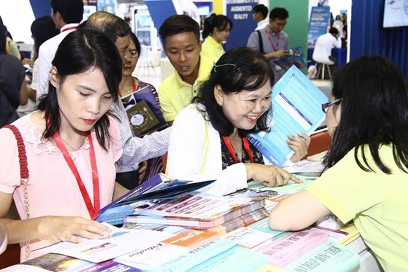 Visitors purchase tours at a display booth. (Photo: Sggp)