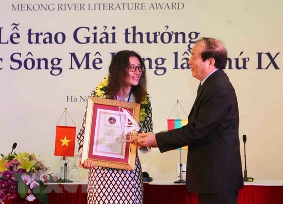 Poet Huu Thinh, President of Vietnam Union of Literary and Arts Associations  presents an award to a writer. (Photo: VNA)