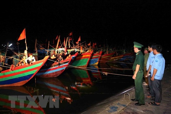 A team of border guards and representatives from the Cua Sot fishing port's management board in Ha Tinh province carry out a patrol in a shelter area for boats (Source: VNA)