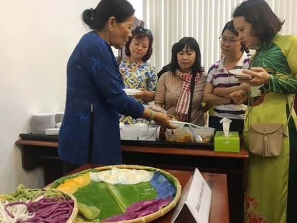 Pastry chef Truong Thi Chieu (L) introduces her cakes to visitors at the press conference of the vent. (Photo: Sggp)