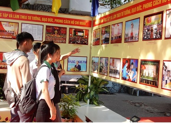 "Students visit the exhibition on ""Study and Follow Ho Chi Minh's Moral Example""."