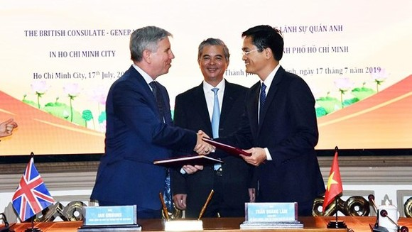 Ian Gibbons, Consul General of the UK in Ho Chi Minh City ( L) and director of the HCMC's Department of Transport, Tran Quang Lam hands over agreements. (Photo: VNA)