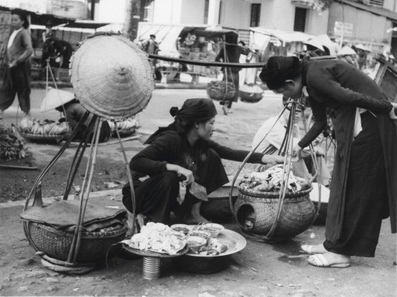 A vendor fills the baskets with goods.